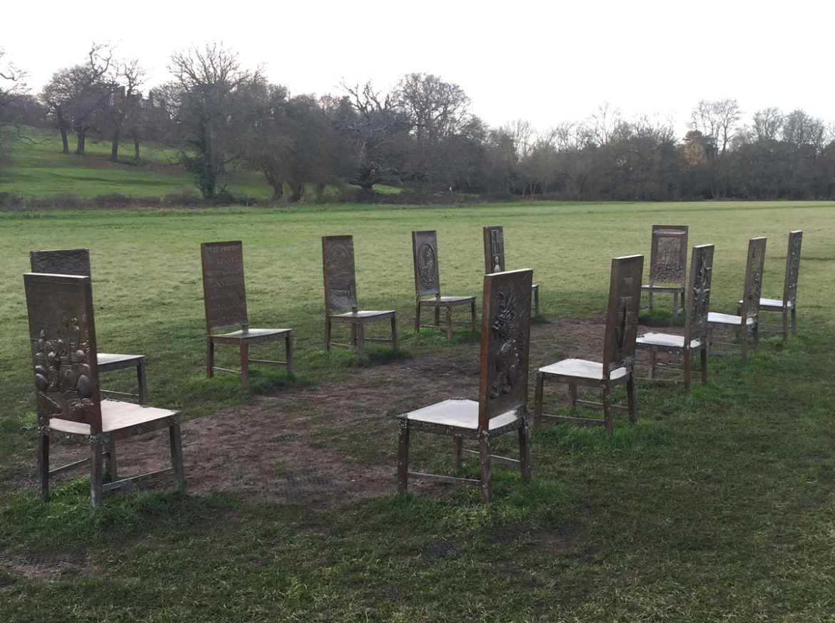 The jurors is an immersive sculpture or 12 bronze chairs seen in the meadow at Runnymede