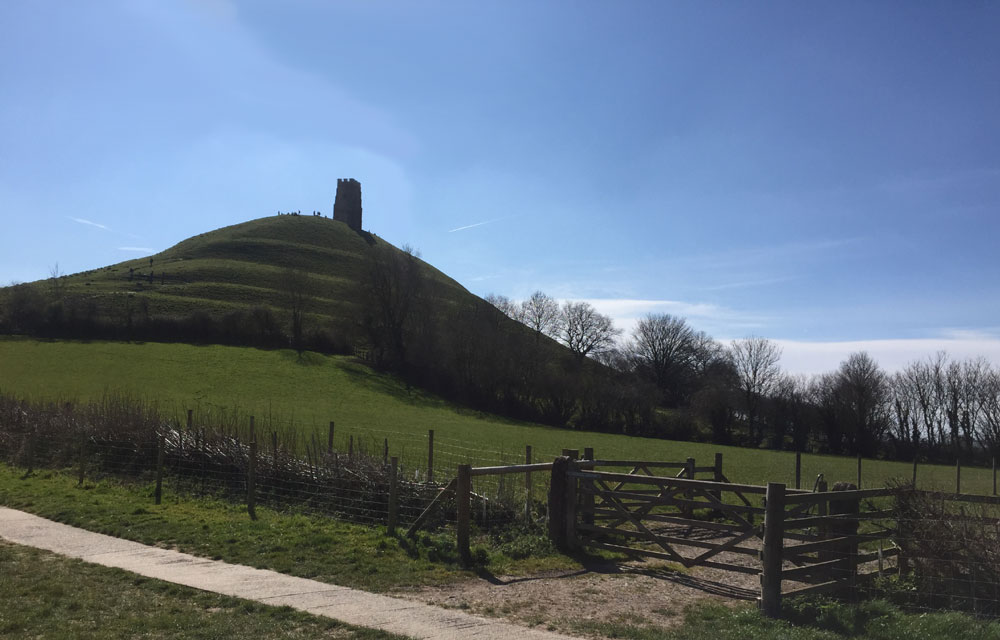 View of Glastonbury Tor, Green fields and hill with tower on top with blue sky