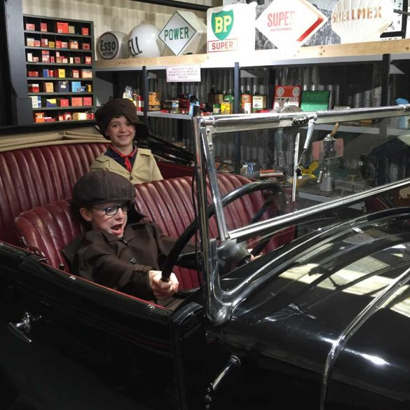 Two boys sitting in old car at Haynes Motor Museum in Somerset
