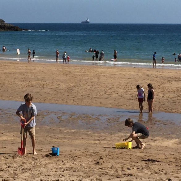 Children playing on Saundersfoot Beach, Pembrokeshire, Wales