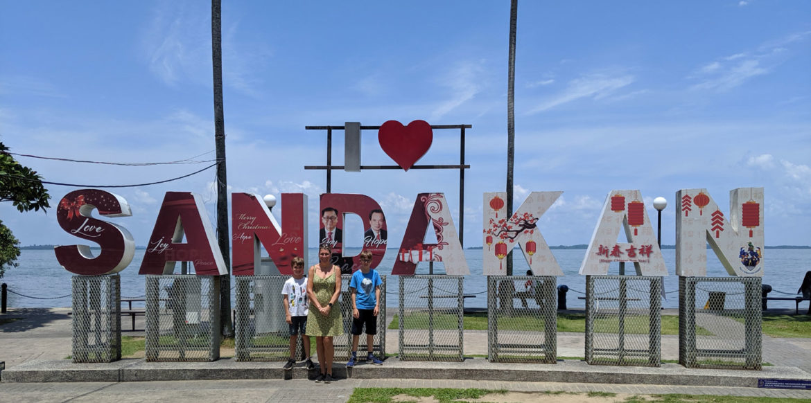 Family standing in front of I love Sandakan sign