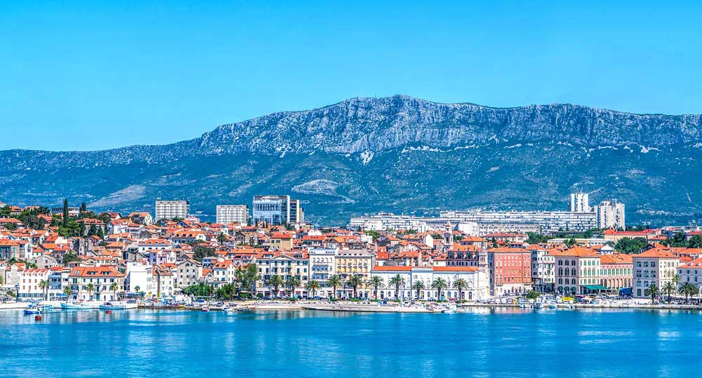 view of the waterfront in Split, Croatia from sea flanked by high cliffs