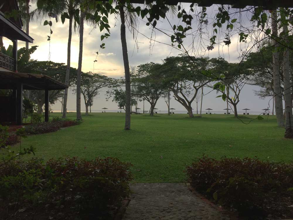 veranda view of lawns, trees and sea in distance at Nexus Beach Resort in Borneo