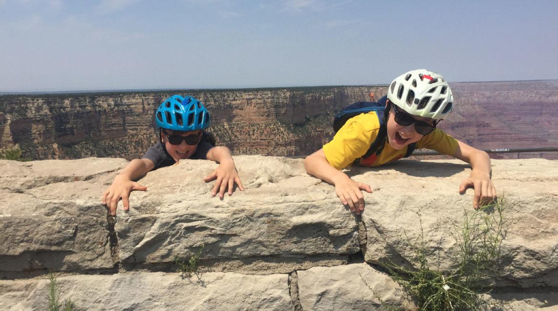boys pretending to climb up ridge at Grand Canyon