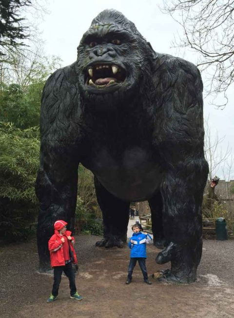 Two small boys under arms of giant Gorilla at Wooky Hole in Somerset