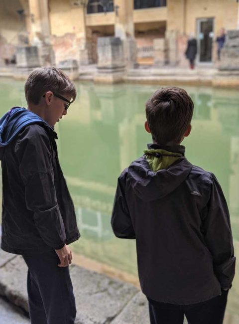Boys looking at Roman Baths, Somerset, England