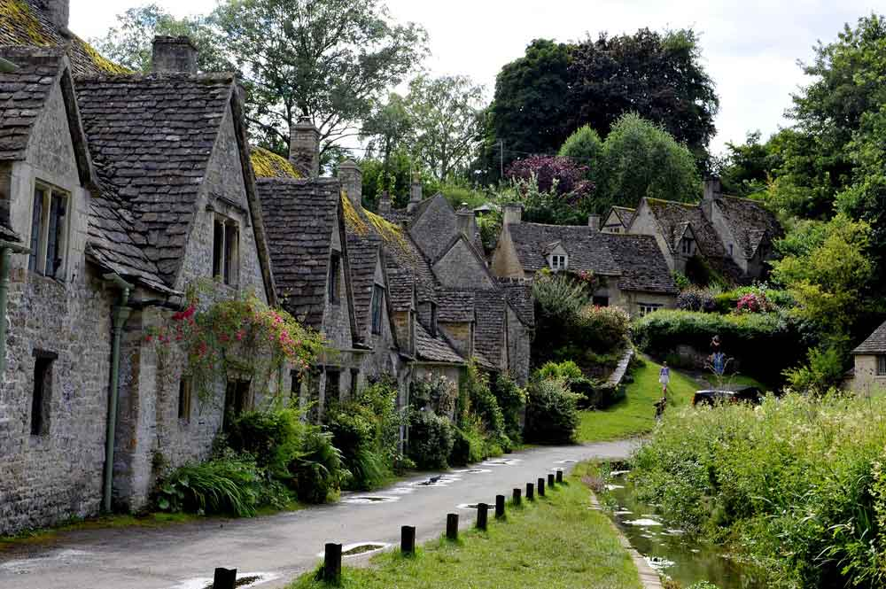 View of quaint Cotswold village, stone houses nestled amongst trees