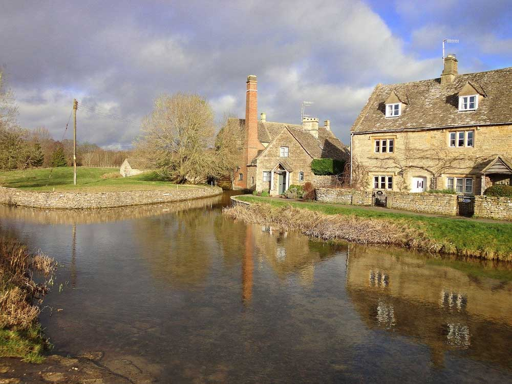 view across stream to brown stone Cotswolds cottages and Mill, Lower Slaughter, Cotswolds UK