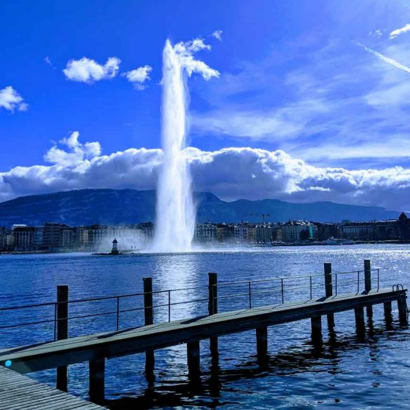View of the Jet d'Eau on Lac leman Geneva, blue skies, a pier and cloud covered mountain