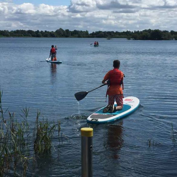 Two boys setting off across Cotswold Water Park Lake
