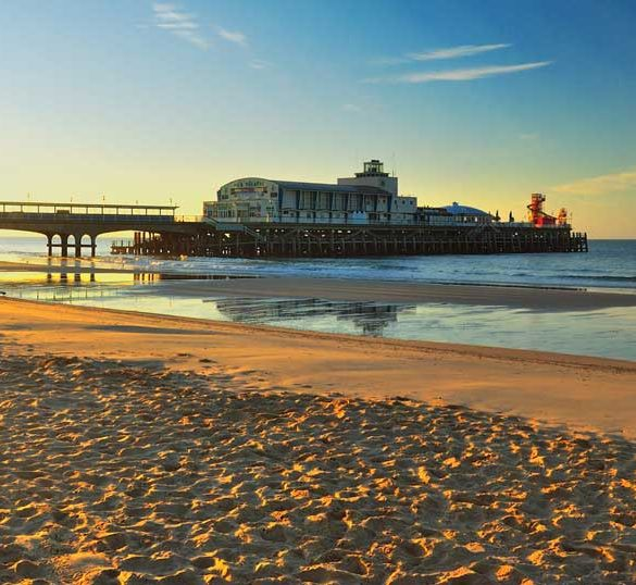 View of Bournemouth pier at sunset from beach, Dorset, England