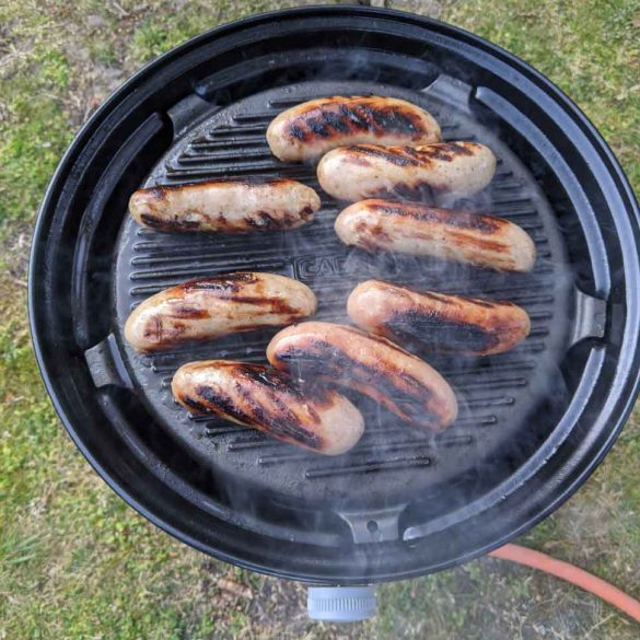 Sausages cooking on a Cadac gas grill on camping trip