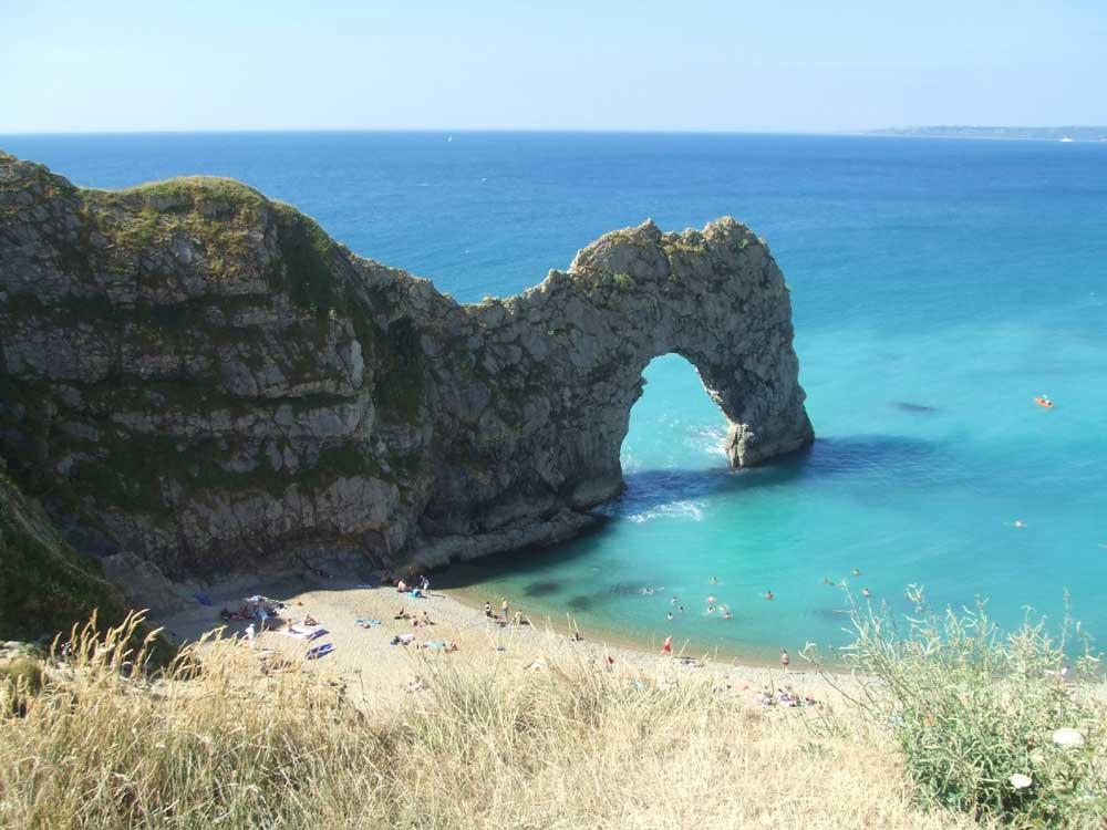 view of Durdle Door, blue sea, sand, Dorset, England