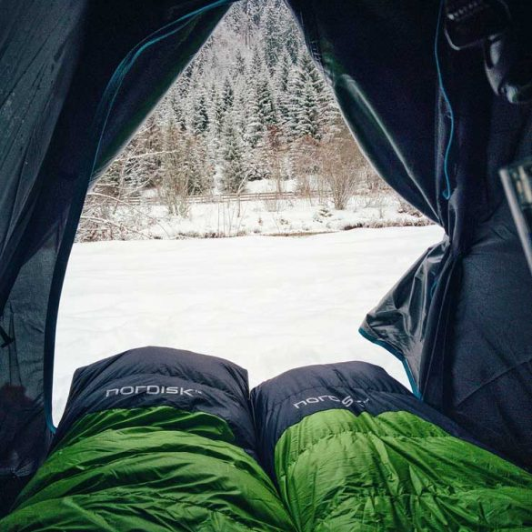 view of snowy field and forest from two sleeping bags in tent