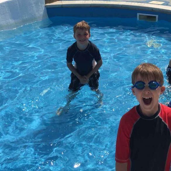 Boys having fun in the Wilksworth farm swimming pool, Dorset, England