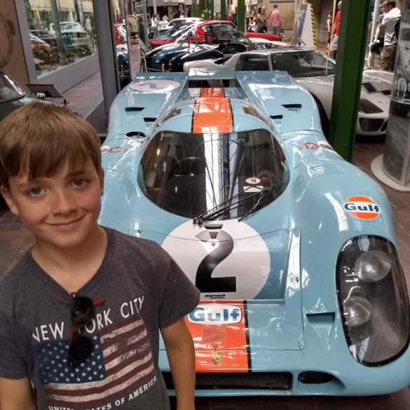 Boy in front of Gulf Porsche at Beaulieu Motor Museum, Hampshire