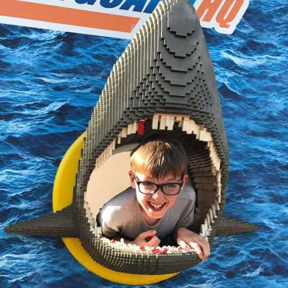 small boy in mouth of Lego shark at Legoland near Windsor, Berkshire, England