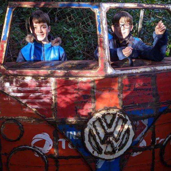 Two boys standing behind Sculpture of VW camper van