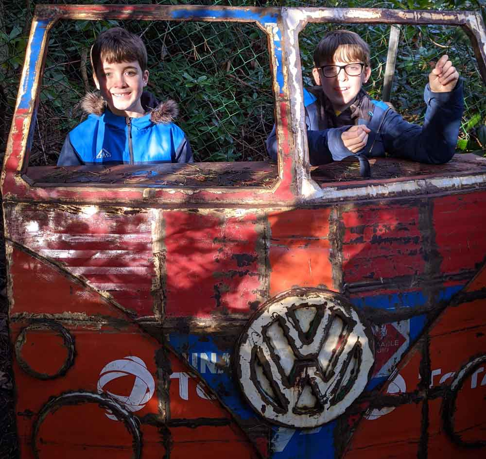 Two boys standing behind Sculpture of VW camper van at the Sculpture Park in Farnham, Surrey
