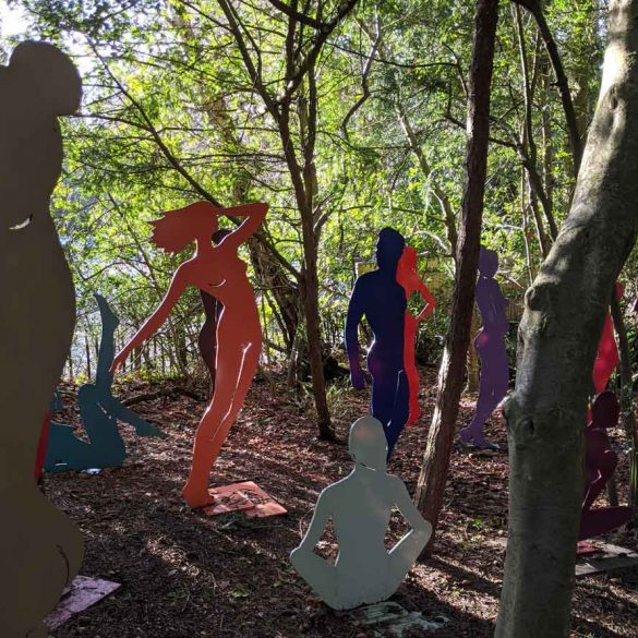 Outlines of bodies standing in woods sculpture