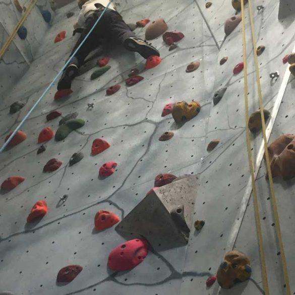 Child indoor climbing at craggy rock, Surrey