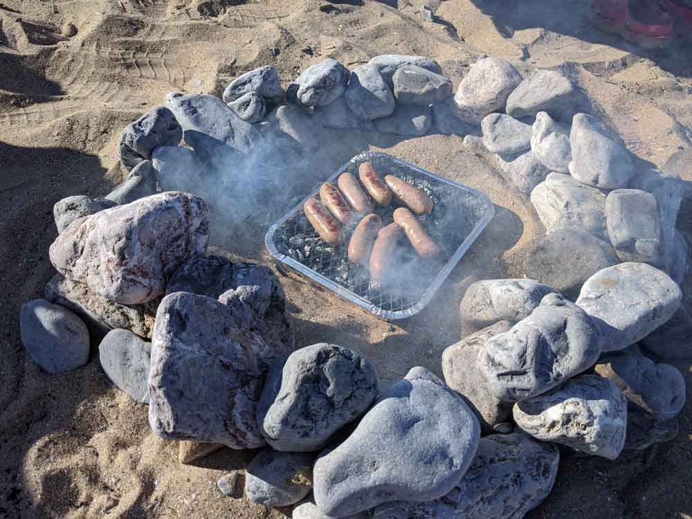 Sausages cooking on a Barbeques on the Beach, Gower Peninsula