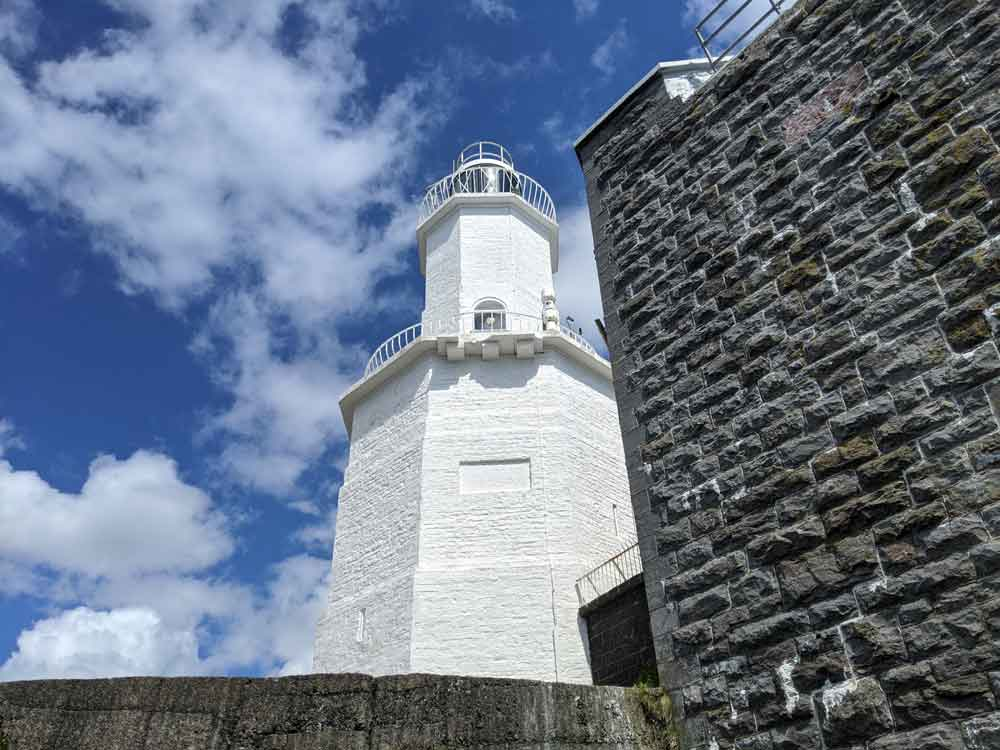 Looking up at white brick painted Mumbles Light House with blue sky and clouds, Gower Peninsula, Wales