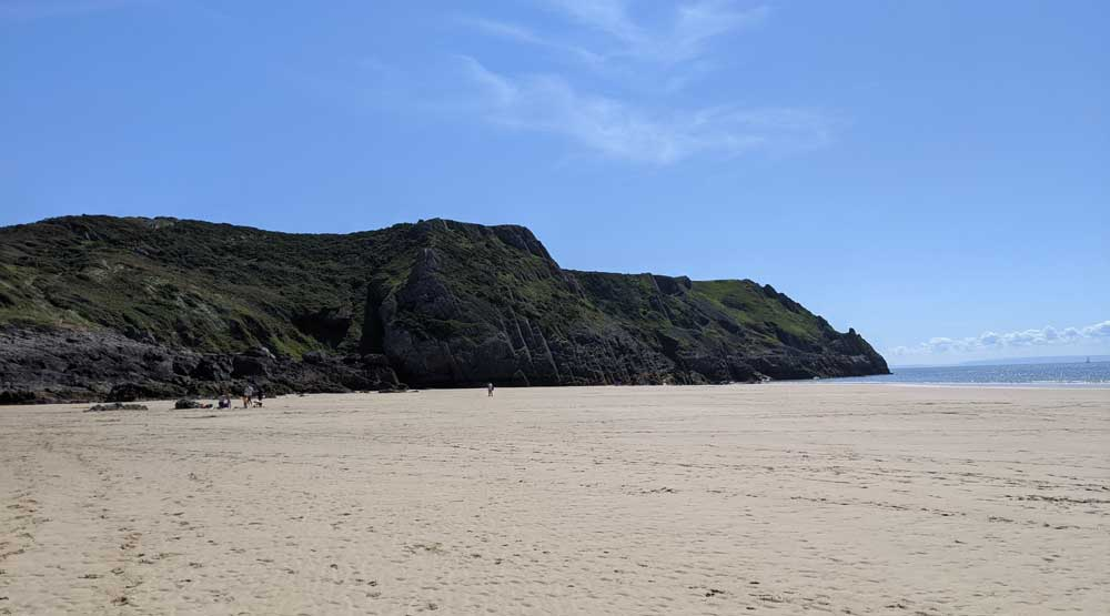 View of sandy beach and green cliffs at Pobbles Bay, Gower Peninsula