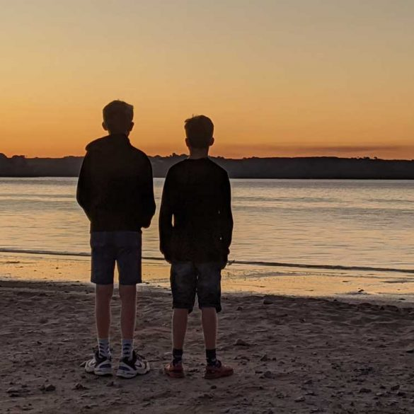 Two boys standing on beach looking out across Oxwich Bay at Sunrise, Gower Peninsula