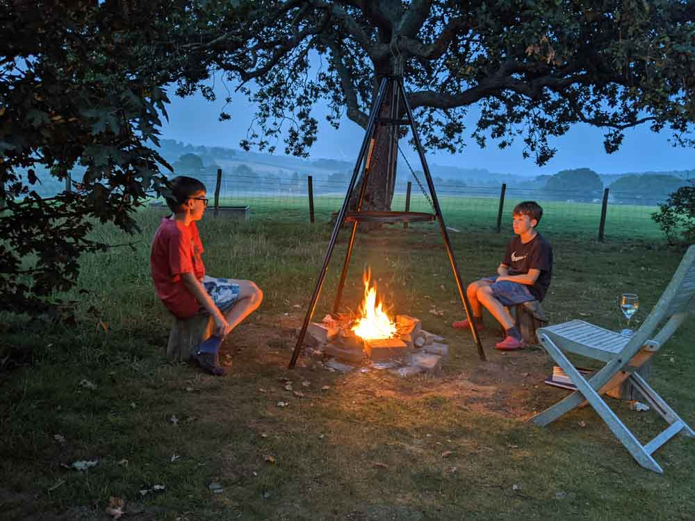 Two boys sitting around early evening Campfire, cooking on Tripod at Freshwinds Camping, Sussex