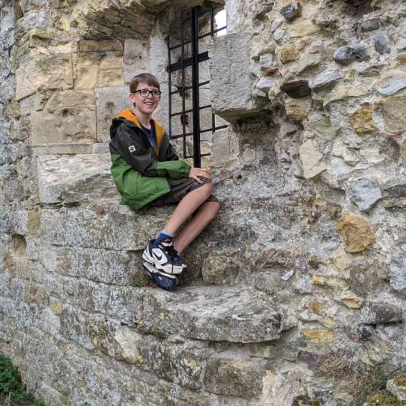 Boy sitting on Castle wall enjoying the view Camber Castle, Rye, Sussex