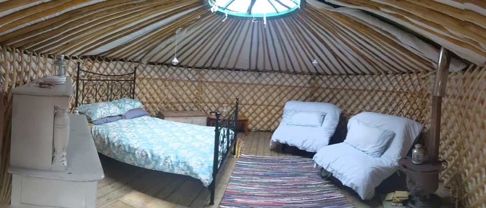 View of cozy beds, log burner and cabinet inside Owl Yurt, Freshwinds Farm, Sussex