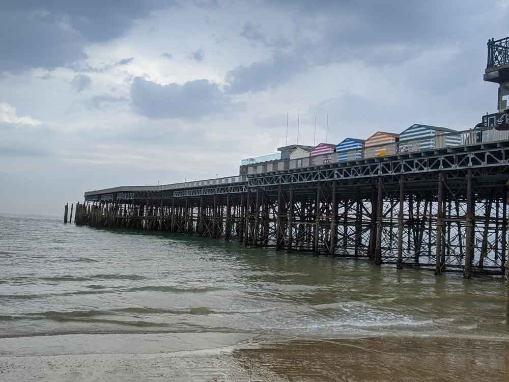 Looking at Hastings Pier from shingle beach with multicoloured stripped beach huts, Hastings, Sussex