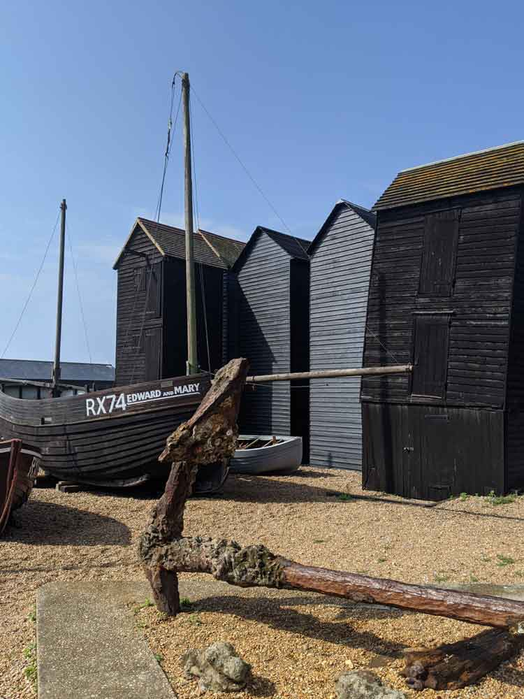 Tall Black painted Net Huts with large Rusty Anchor in foreground, Hastings, Sussex