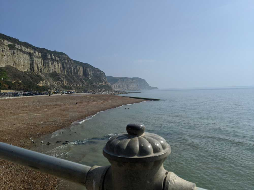 Rock-a-Nore Beach, with calm sea and cliffs behind, Hastings, Sussex