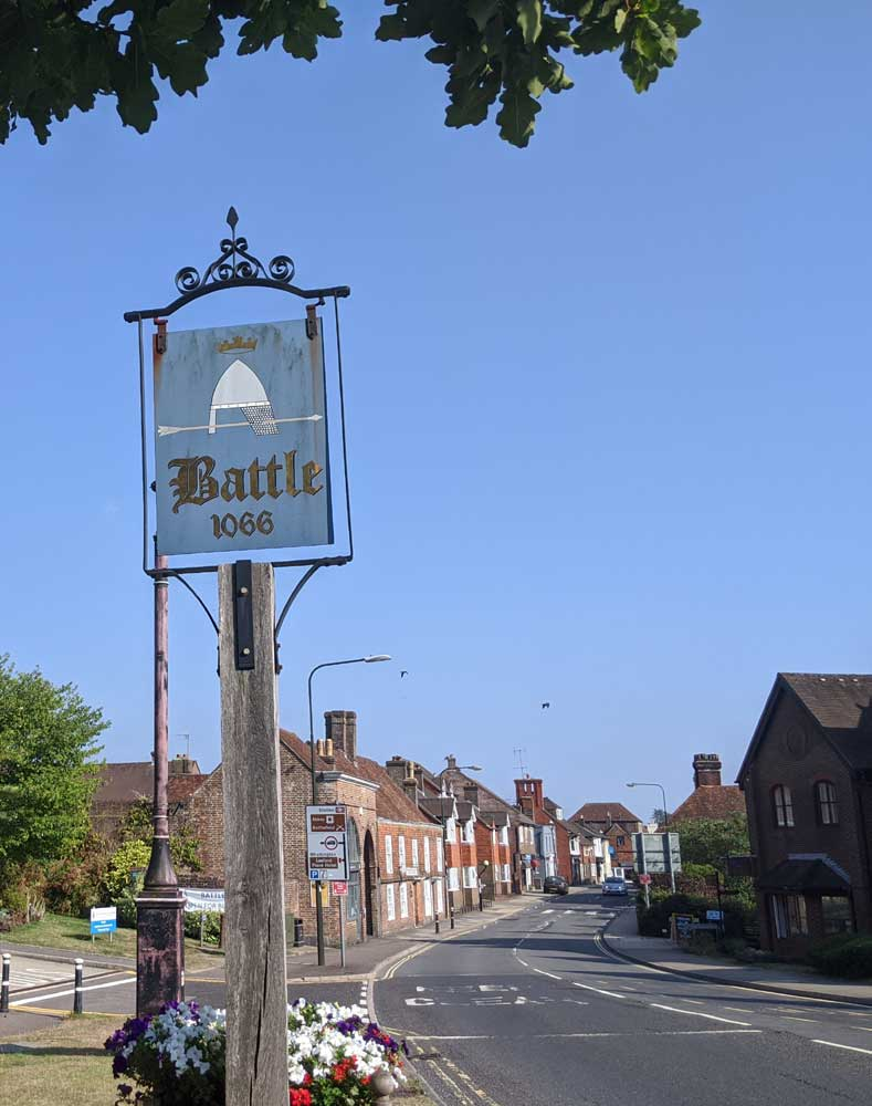 Sign of Town of Battle 1066, with Battle Town highstreet in background, Battle, East Sussex, England