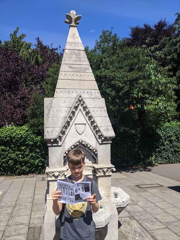 Boy looking at clues for Treasure Trail, Wimbledon, London, UK