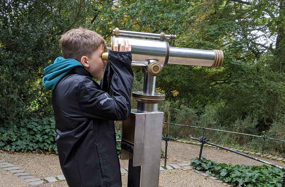 Boy looking through telescope, King Henrys Mound, Richmond Park, London, UK