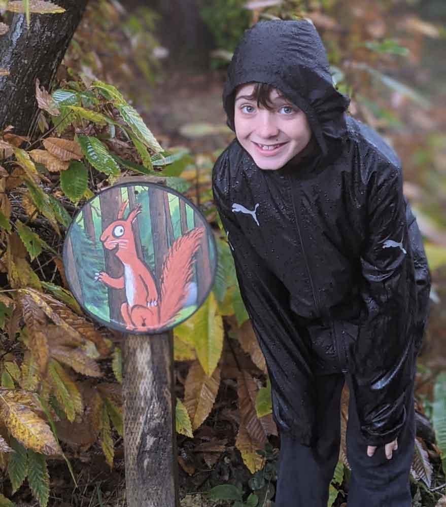 Boy standing next to Gruffalo Trail Sign, Beechenwood Gruffalo Trail, Wye Valley, UK