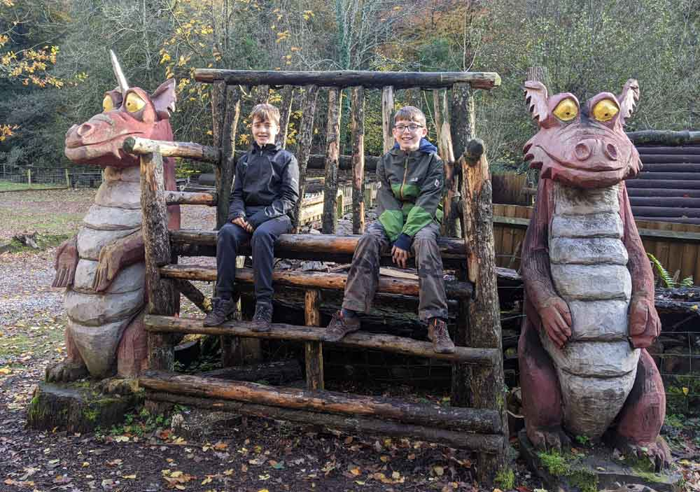 Two boys sitting on Wooden chair flanked by two large Dragon Sculptures at Dean Heritage Centre, Wye Valley, UK