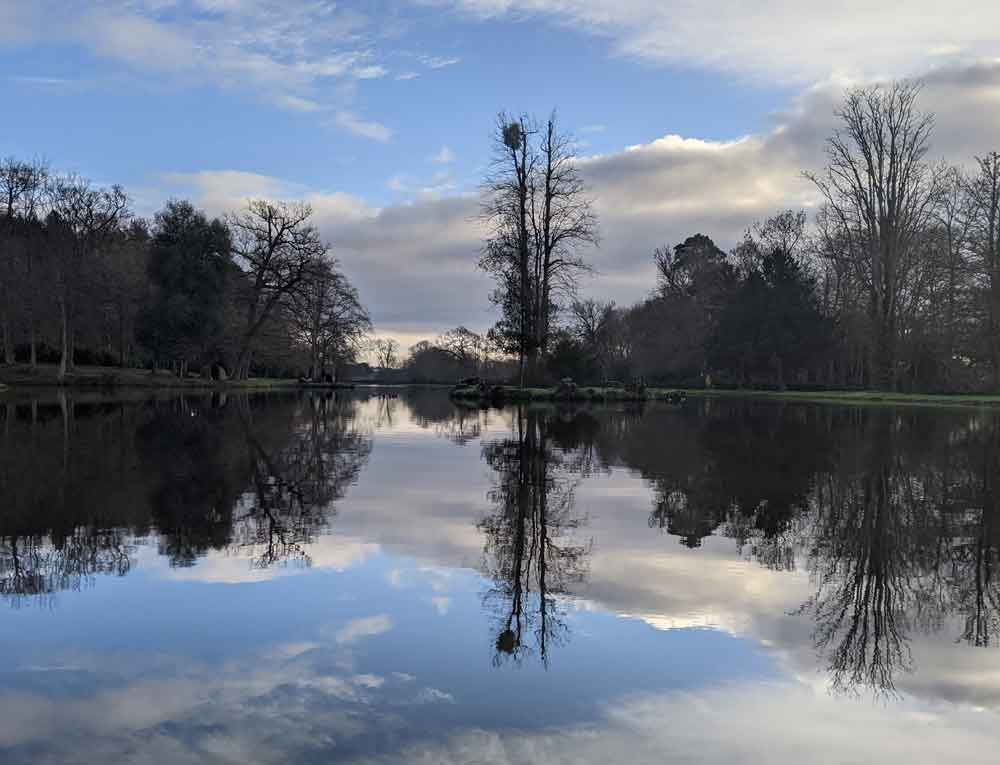 The Mirror image of clouds and trees in lake at Painshill Park, Surrey, UK
