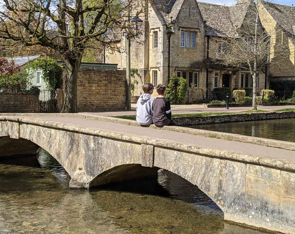 Two boys sitting at Bourton on the Water, Cotswold, UK