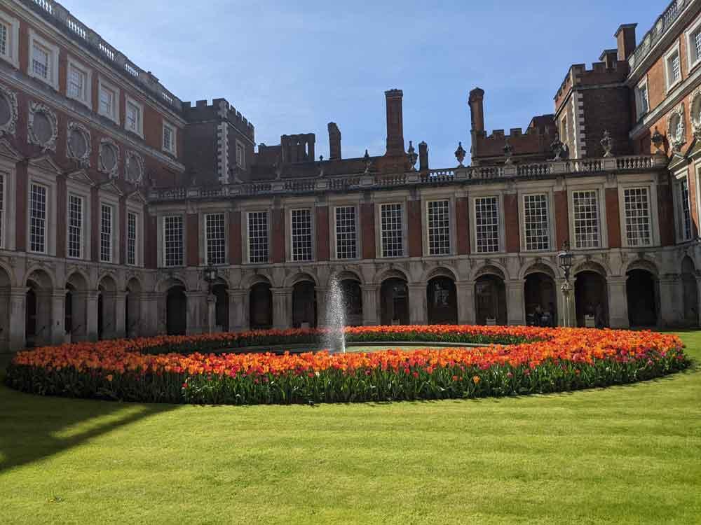Ring of bright Tulips surrounding fountain at Hampton court Palace courtyard, Surrey, UK