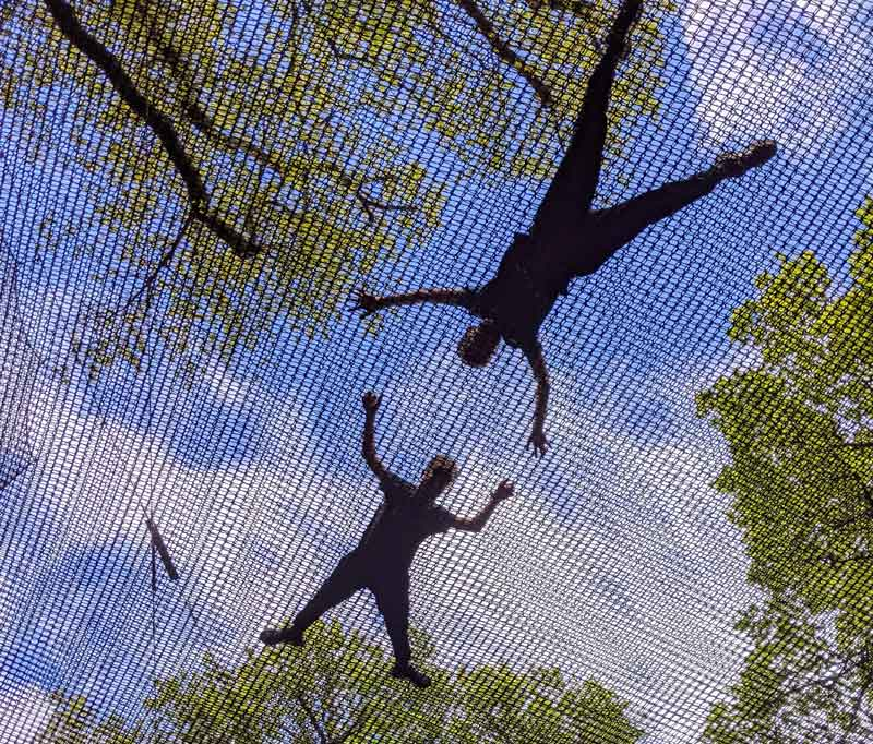 Looking up at silhouettes of boys at Black Park Nets, Buckinghamshire, UK
