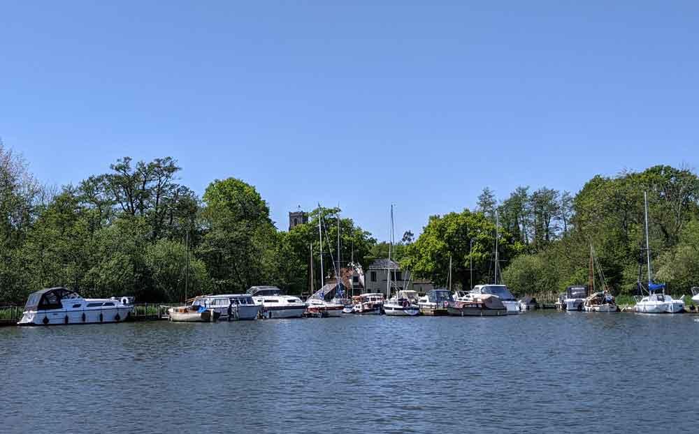 Boats moored at Malthouse Broad, Norfolk Broads, Norfolk, UK
