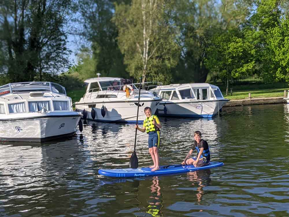 Two boys on paddle board having fun on water at Beccles
