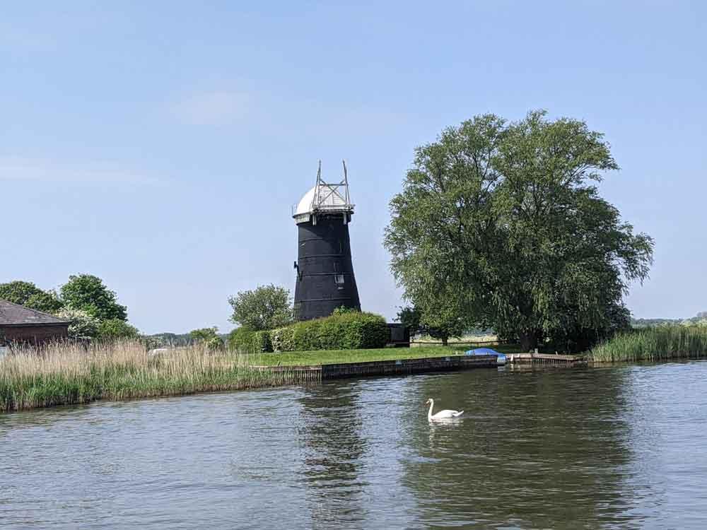Restored Windmill beside the river, Norfolk Broads, Norfolk, UK